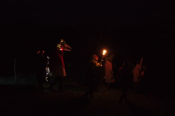 People in the dark with torch dressed for a wassail.